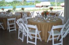 sillas blancas de madera, mesas redondas, mantel c